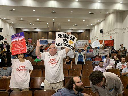 """白人家长David Rem拿着""""你太无耻,种族主义者卡兰萨""""的牌子和华裔家长一起高喊,要求教育总监下台。"""
