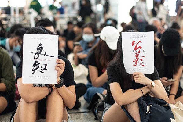 周二(8月13日)香港市民再次聚集在香港國際機場舉行反對有爭議的引渡法案,有示威者手「「良心」和「正義」的牌子表達訴求。(Philip FONG/AFP)