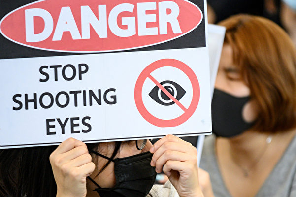 周二(8月13日)香港市民再次聚集在香港國際機場舉行反對有爭議的引渡法案,有示威者手持用英文寫的「停止射擊眼睛」的標語牌,抗議警方濫用武力。(Philip FONG/AFP)