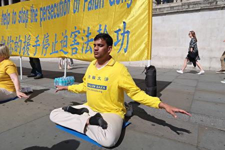 8月29日,來英國參加歐洲法會的印度小伙子拉維‧科爾盧(Ravi Kollu)在鴿子廣場洪法。(詹娜/大紀元)