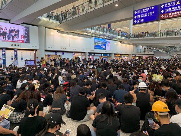 2019年8月9日,香港機場萬人接機,參加者持各式海報和標語在大堂靜坐。(駱亞/大紀元)