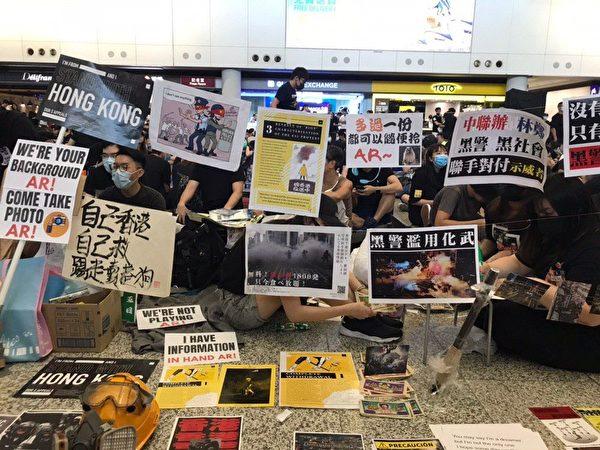 2019年8月10日,萬人機場送機,參加者持各式海報和標語在接機大堂。(林卓楷/大紀元)