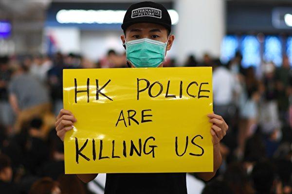 2019年8月12日,「百萬人塞爆機場」在赤鱲角機場展開。圖為民眾持「香港警察正在殺我們」的英文展板。(MANAN VATSYAYANA/AFP/Getty Images)