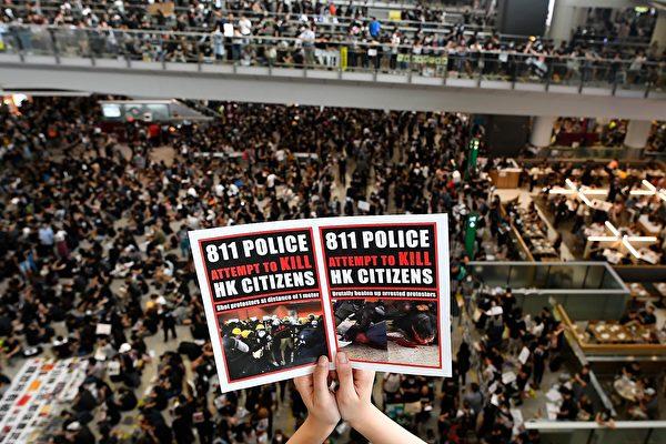 2019年8月12日,「百萬人塞爆機場」在赤鱲角機場展開。圖為民眾持傳單表達訴求。(MANAN VATSYAYANA/AFP/Getty Images)