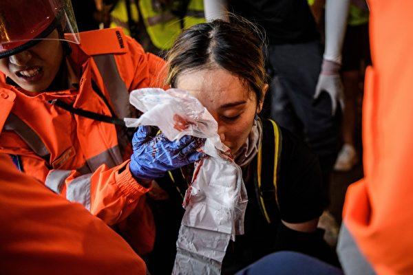 2019年8月11日晚,香港尖沙咀,一名女性眼睛中彈,救護人員緊急為她包紮。(ANTHONY WALLACE/AFP/Getty Images)