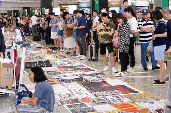 2019年8月14日,香港機場,許多旅客在觀看反送中人士貼的展板。(宋碧龍/大紀元)