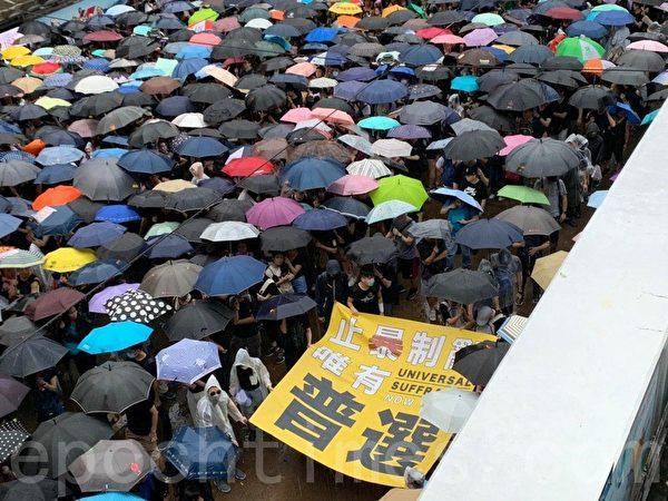 2019年8月18日,參加維園集會的民眾,在雨中往維園方向前進。(駱亞/大紀元)