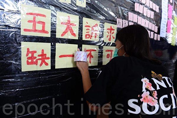 2019年8月22日,香港中學生在中環愛丁堡廣場舉辦「反修訂條例」集會活動。學生在連儂牆上貼「五大訴求 缺一不可」。(宋碧龍/大紀元)