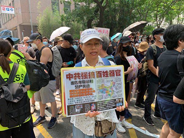 2019年8月24日,觀塘駿業公園的人們在等待遊行。遊行人士舉著自製看板。(駱亞/大紀元)