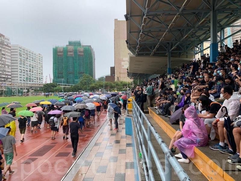 由於看台已坐滿人,市民撐著雨傘站在運動場的跑道上。(駱亞/大紀元)