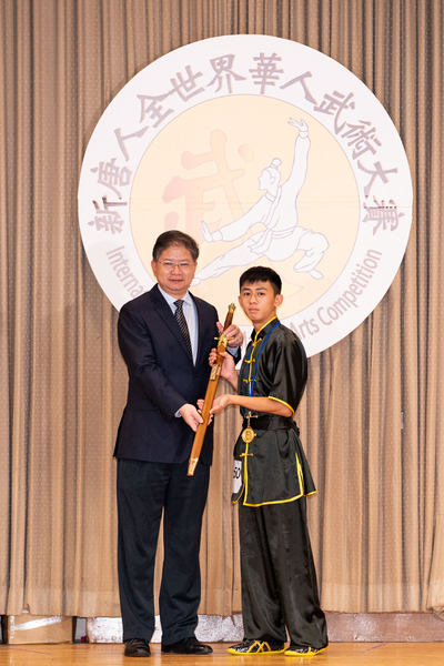大紀元新唐人媒體集團總裁唐忠(左)將一把日月紫微劍頒發給少年拳術組金獎得主莊宗廷(右)。(戴兵/大紀元)