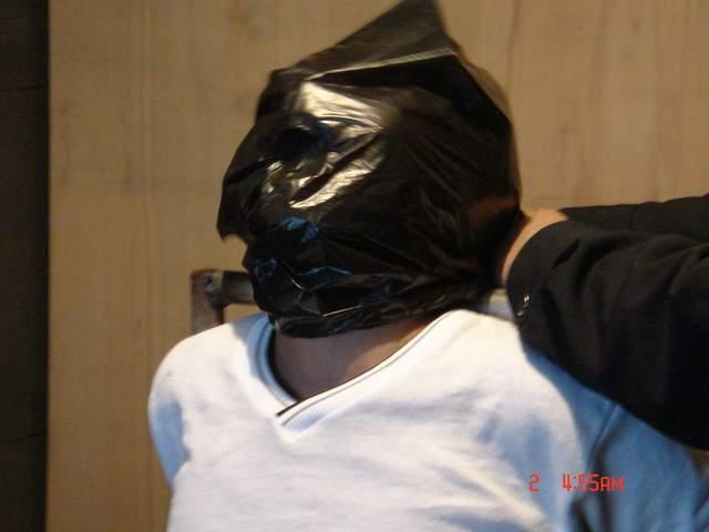 酷刑演示:膠袋窒息。(明慧網)
