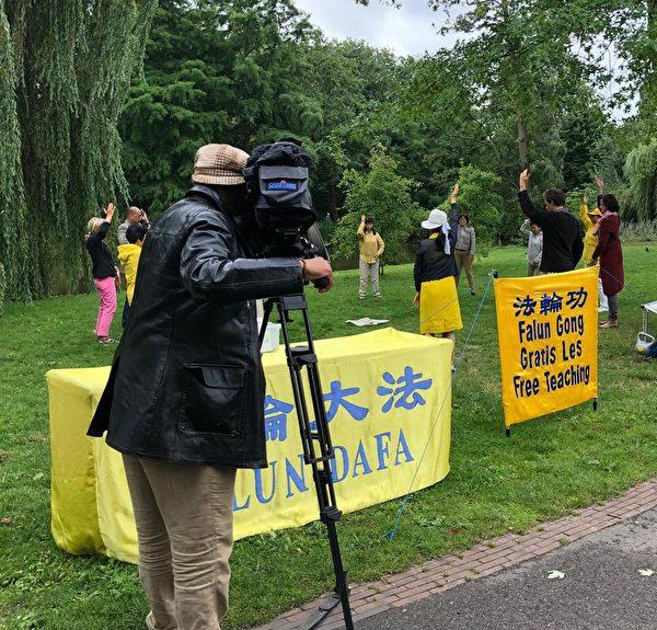 荷蘭阿姆斯特丹AT5電視台拍攝並採訪了在公園裏煉功的法輪功學員們。(明慧網)