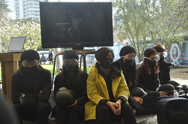 集會中坐在最前方的香港學生。(易凡/大紀元)
