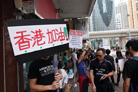 香港反送中,在前面集會地點的路上,有市民舉起「香港加油」和五大訴求的標語。(余鋼/大紀元)