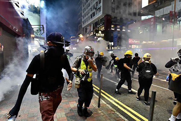 8月4日晚,在銅鑼灣,警察開始發射催淚彈,驅散示威者。(ANTHONY WALLACE/AFP/Getty Images)