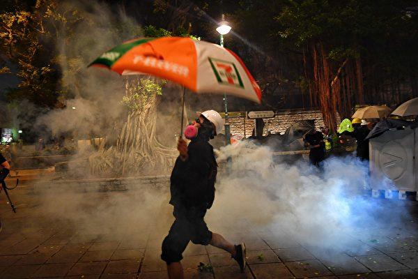 8月11日,香港深水埠,示威者將警方發射的催淚彈扔擲回去。(MANAN VATSYAYANA/AFP/Getty Images)