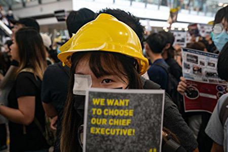 8月11日香港警察近距離用布袋彈擊中一位抗議少女,右眼被射穿;8月12日港人在機場矇右眼抗議。(Anthony Kwan/Getty Images)