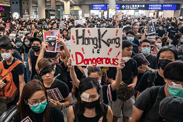 8月11日,一位女救護員遭港警射穿右眼,圖為8月12日,港人在機場蒙右眼抗議,一名女士手舉英語標語:「香港危險」。(Anthony Kwan/Getty Images)