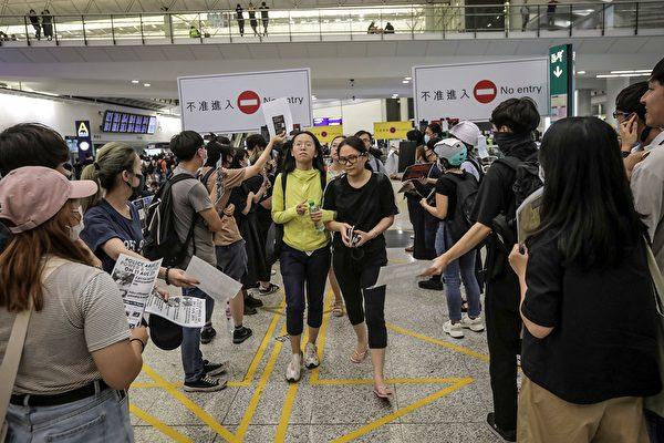 港人向最後到達的飛機旅客致敬,並遞上「反送中」傳單。(VIVEK PRAKASH/AFP/Getty Images)