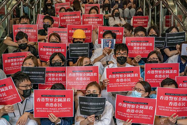 8月13日,大批港人繼續在機場抗議港警8.11施暴,手舉標語。(Anthony Kwan/Getty Images)