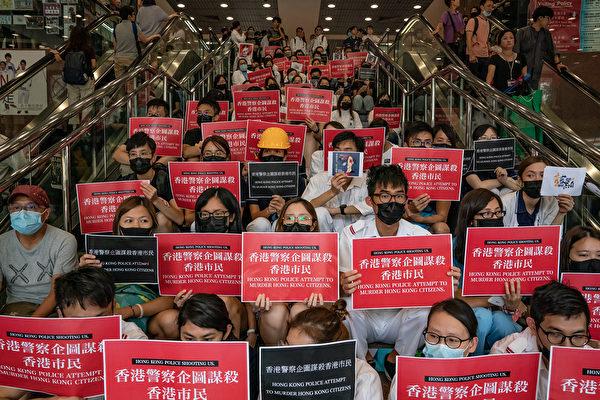 8月13日,大批港人繼續在機場抗議港警8.11施暴,手舉標語。( Anthony Kwan/Getty Images)