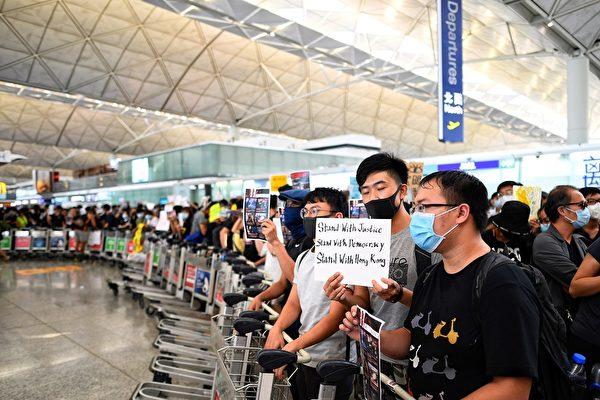 8月13日,大批港人繼續在機場抗議港警8.11施暴,手舉標語,迎接旅客。(MANAN VATSYAYANA/AFP/Getty Images)