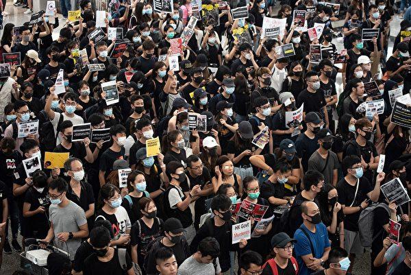 8月13日,大批港人繼續在機場抗議港警8.11施暴,手舉標語。( PHILIP FONG/AFP/Getty Images)