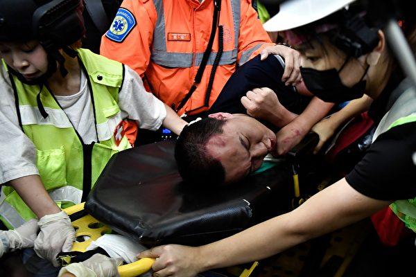 8月13日晚,機場示威者圍追一名疑似大陸公安的男子徐錦煬,這名男子突然暈過去,醫護人員上前救助。(ANTHONY WALLACE/AFP/Getty Images)