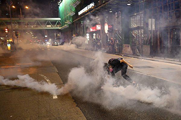 8月14日晚,香港深水埗,防暴警放多枚催淚彈,市民驚恐,示威者滅火。(MANAN VATSYAYANA/AFP/Getty Images)