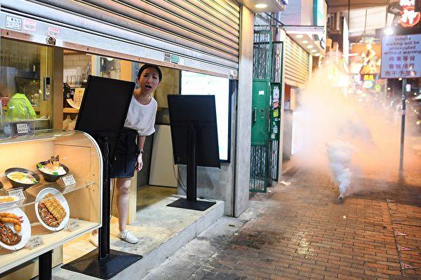 8月14日晚,香港深水埗,防暴警放多枚催淚彈,市民驚恐。(MANAN VATSYAYANA/AFP/Getty Images)