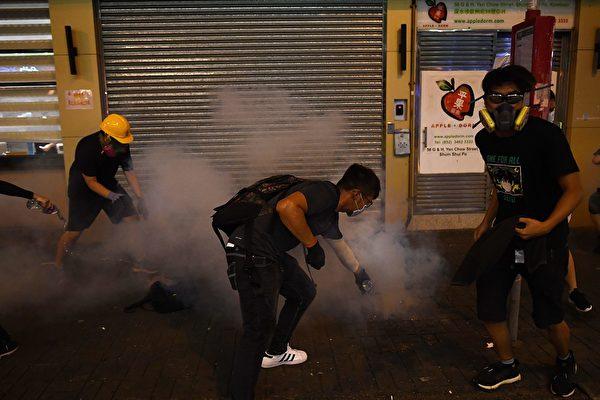 8月14日晚,香港深水埗,防暴警放多枚催淚彈,示威者滅火。(MANAN VATSYAYANA/AFP/Getty Images)