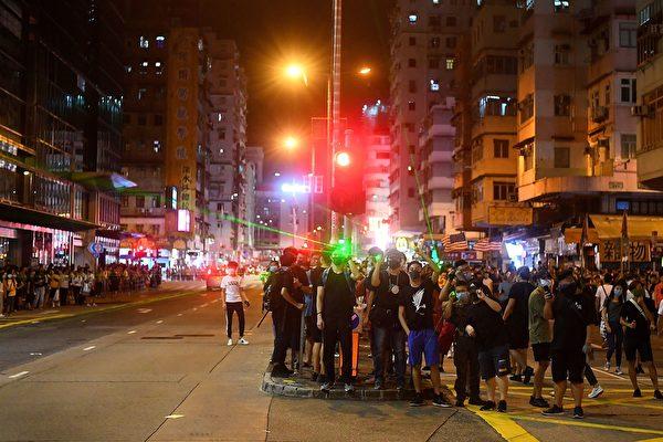 8月14日晚,香港深水埗,防暴警放多枚催淚彈,示威者聚集抗議。(MANAN VATSYAYANA/AFP/Getty Images)