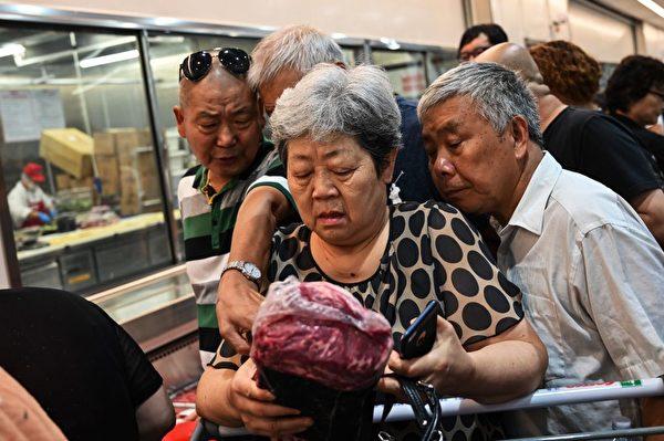 搶肉的大媽。 (HECTOR RETAMAL/AFP/Getty Images)