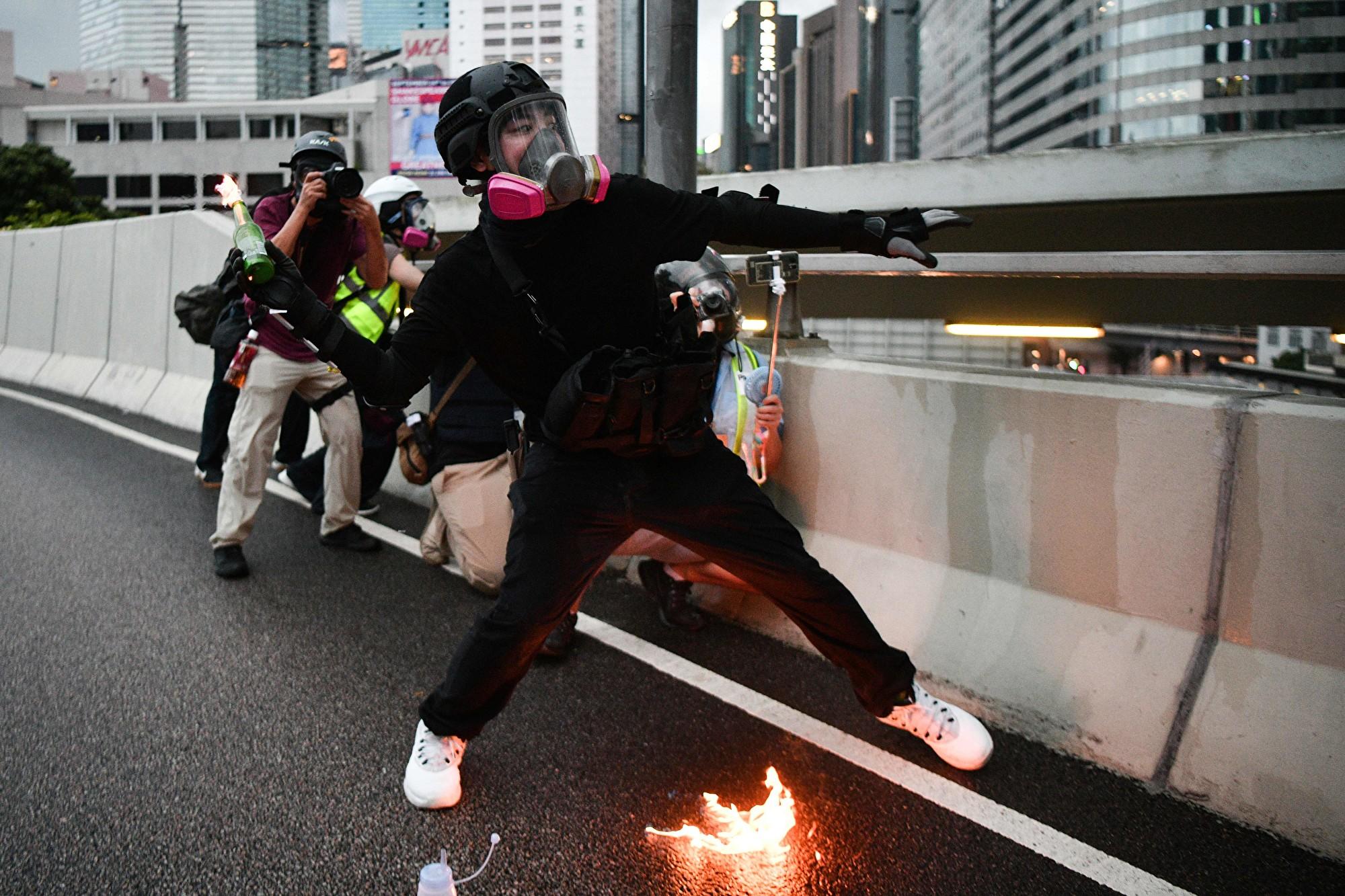 一名黑衣人士點燃汽油彈欲丟擲,腰間的槍枝因動作太大而暴露出來,遭網友懷疑警方「自編自導自演」。(ANTHONY WALLACE/AFP/Getty Images)