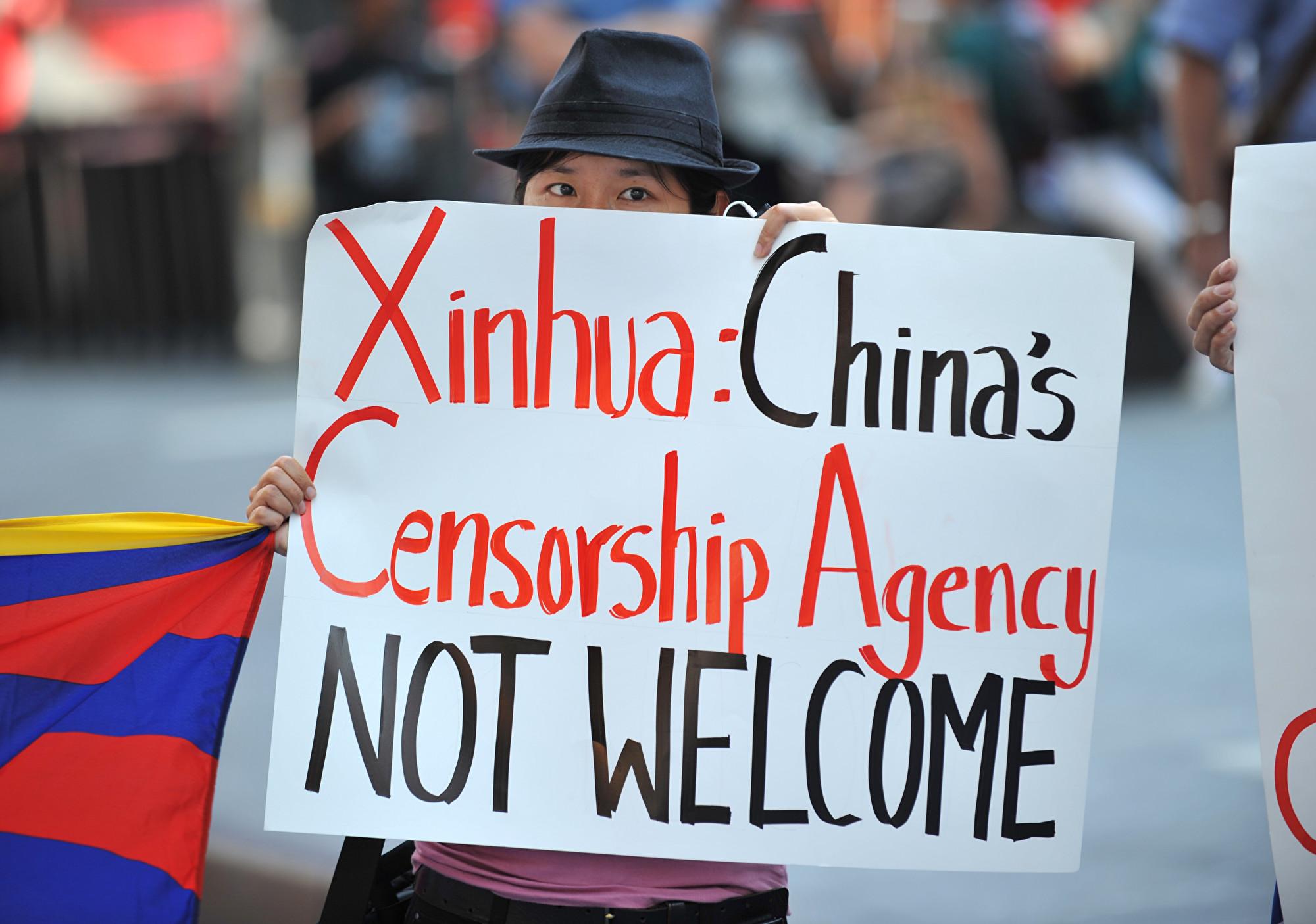 圖為抗議人士在紐約時代廣場的新華社大屏幕前舉牌抗議。(STAN HONDA/AFP/Getty Images)
