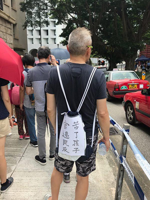 從事電腦工作的李先生自製標語並掛在背囊上,「官逼民反 苦了孩子」。(大紀元)