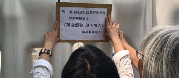特首辦無人接信,銀髮族民眾將信貼在特首辦門外的水馬上。(大紀元)