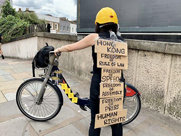 留英港人自發組成單車隊,於8月3日推出新一輪廣告之際,於穿上香港前線示威者的裝束,於倫敦市中心起行至電子廣告牌附近位置參加集會,沿路引起途人關注。(唐詩韻/大紀元)