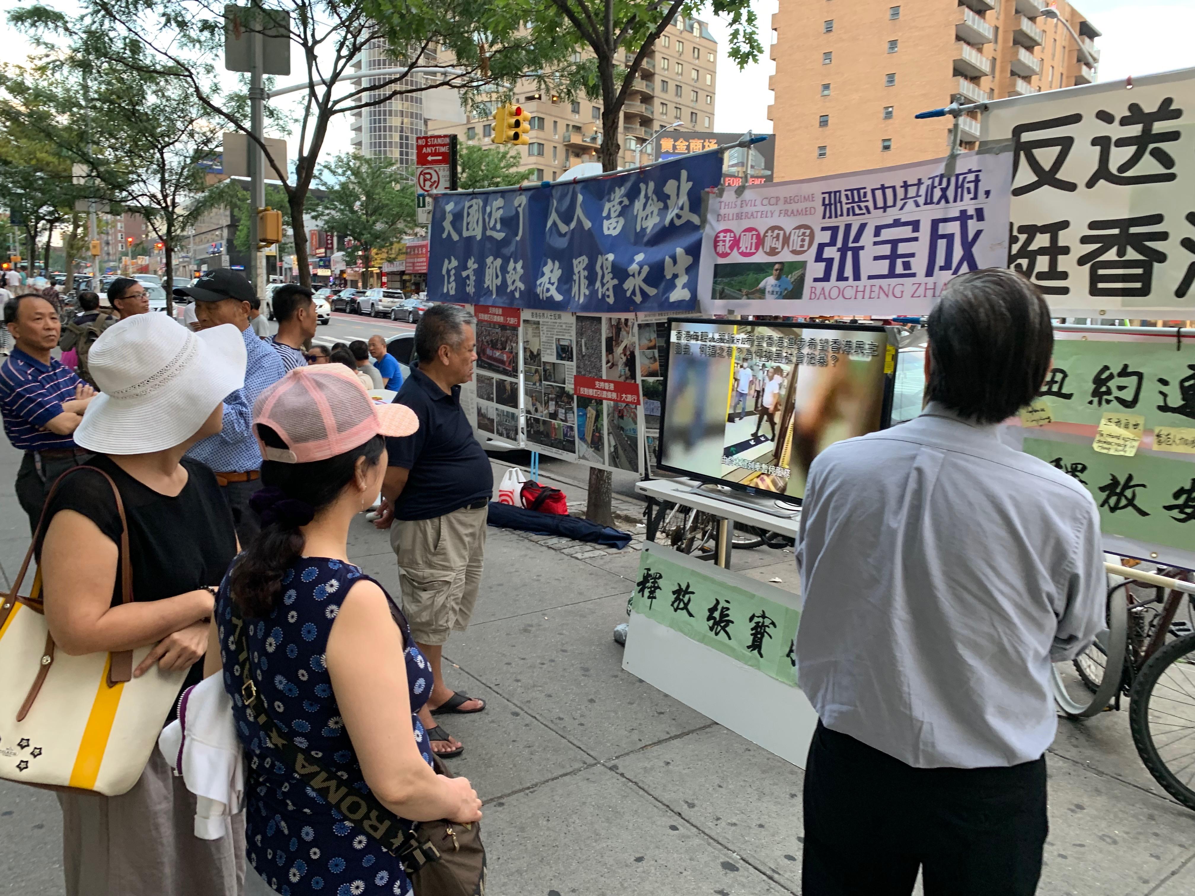部份華人在法拉盛圖書館前築起「連儂牆」,聲援港人反抗中共暴政,吸引路人駐足觀看。 (林丹/大紀元)