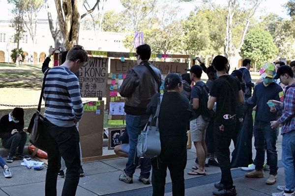 2019年8月9日,香港學生在昆士蘭大學做的流動連儂牆。路過的人在了解信息。(楊裔飛/大紀元)