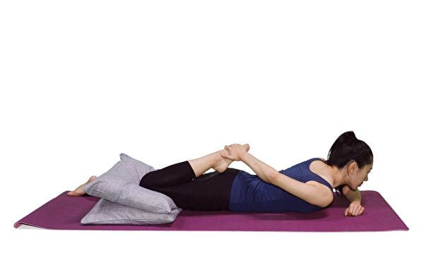 用手握住脚背,向臀部方向拉,直到靠近臀部,伸展大腿前侧的股四头肌。(大纪元)