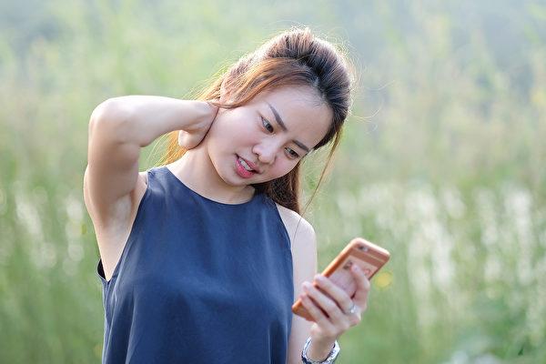 經常滑手機容易造成頸部僵硬疲勞,引起「簡訊頸」症狀。(Shutterstock)