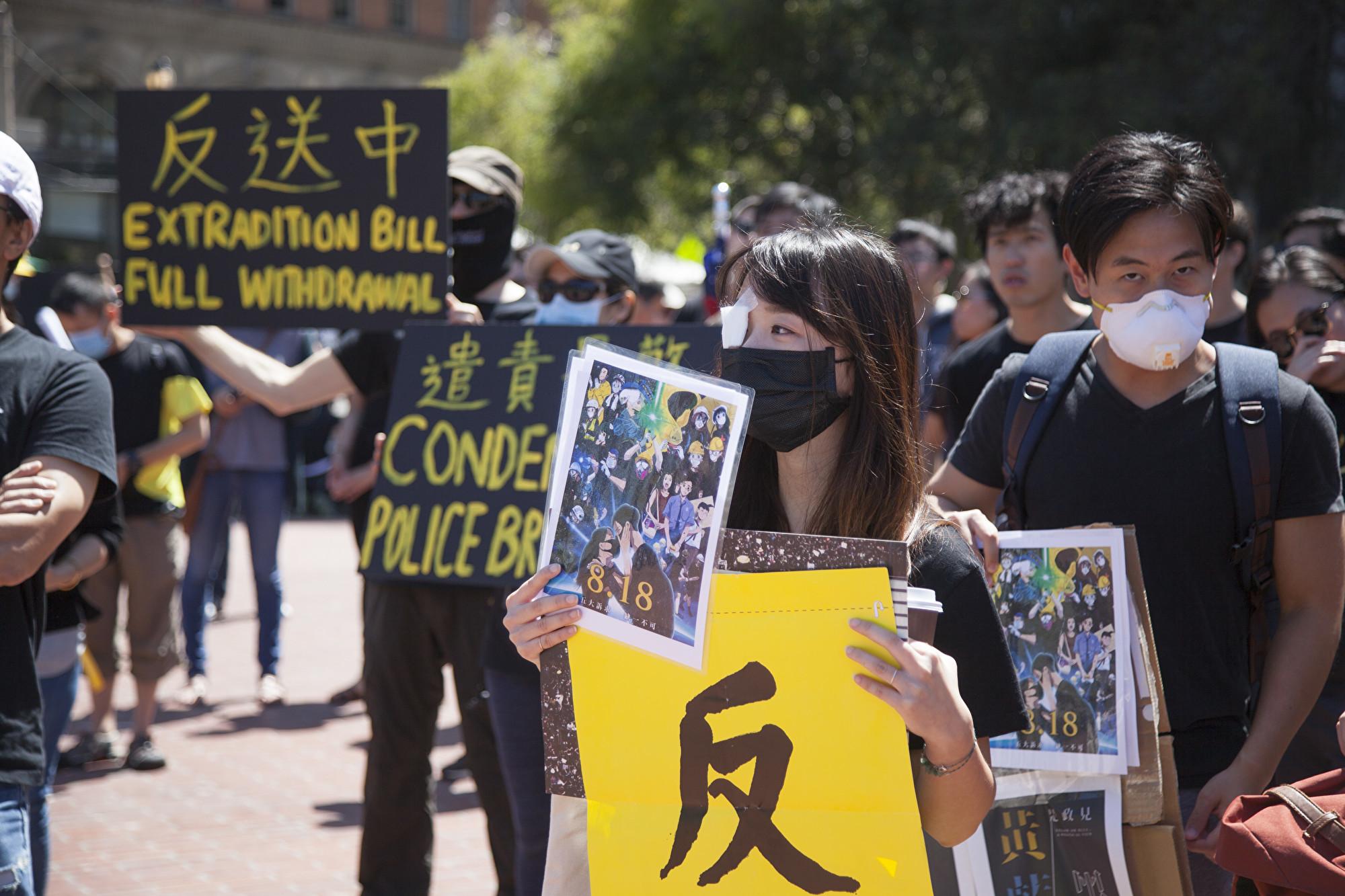 有年輕女士集會上遮蔽右眼,以聲援香港被警方開槍打傷右眼的少女。(周鳳臨/大紀元)