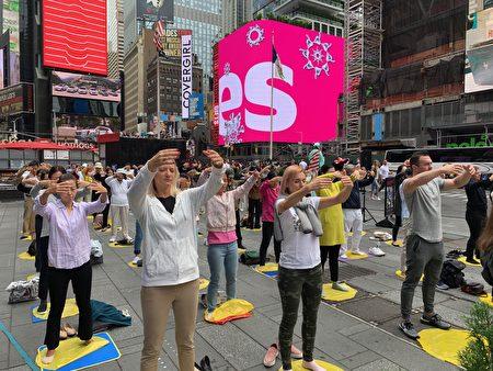 中西法輪功學員在紐約著名景點時代廣場煉功弘法,圖為學員在煉第二套功法——法輪樁法。(林丹/大紀元)