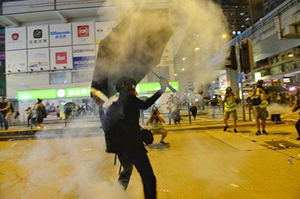 2019年9月6日晚,旺角警署警方開始放催淚彈,其中黑衣人把催淚彈壬回警方。(宋碧龍/大紀元)
