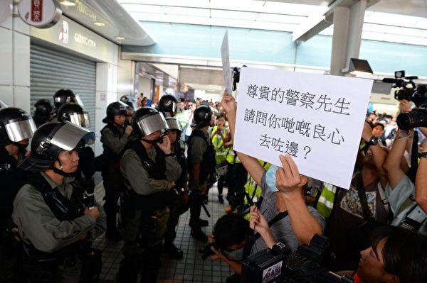 2019年9月7日,東涌站示威者拿標語牌給警察看。(宋碧龍/大紀元)