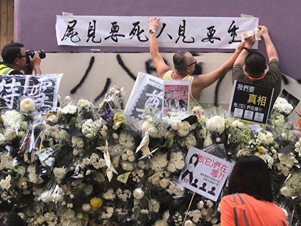 2019年9月7日傍晚,香港民眾聚集在港鐵太子站外現場貼滿許多標語牌與鮮花。圖為民眾貼上「生要見人 死要見屍」橫幅。 (余天祐/大紀元)