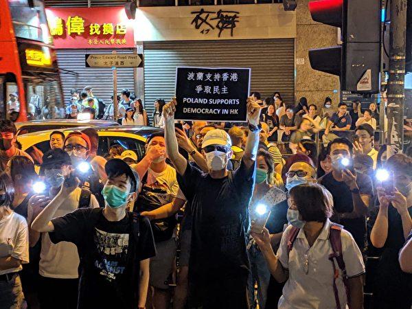 2019年9月7日晚,旺角警署外的部份民眾,舉起手機自帶燈連續高喊:「7.21不見人 8.31打死人」。(黃曉翔/大紀元)