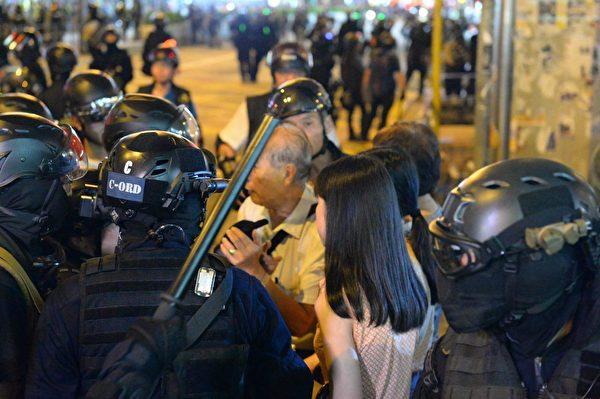 2019年9月7日晚,太子站附近幾十個警察圍著陳伯和一名女孩。(宋碧龍/大紀元)